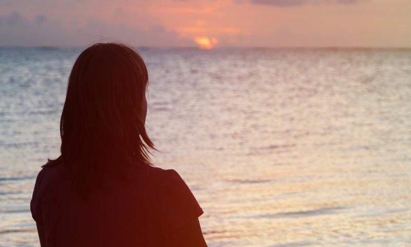 Starke Nerven behalten: Frau schaut im Sonnenuntergang aufs Meer