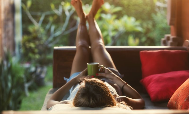 Nahrungsergänzung für starke Nerven & Muskeln: Frau liegt im Garten mit einer Tasse Tee und entspannt.